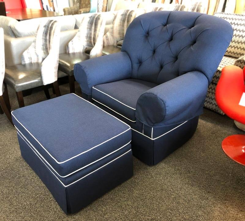 Chair and ottoman reupholstered with dark blue fabric and decorated with skirt.